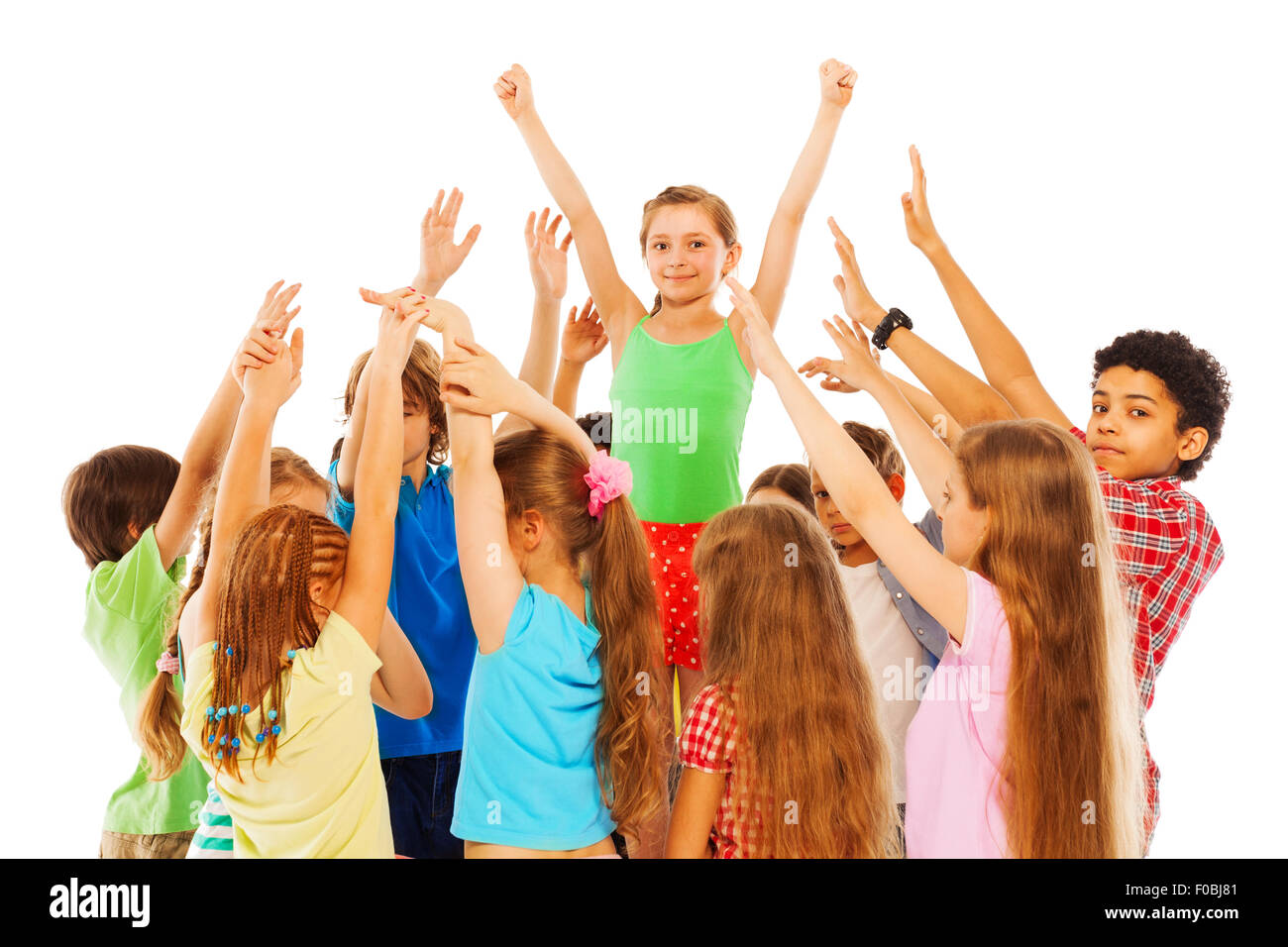 Happy girl with raised hands in group of kids - Stock Image