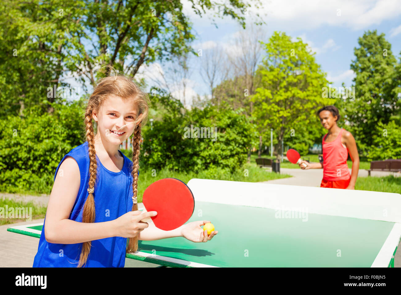 Two Happy Girls Playing Ping Pong Outside   Stock Image