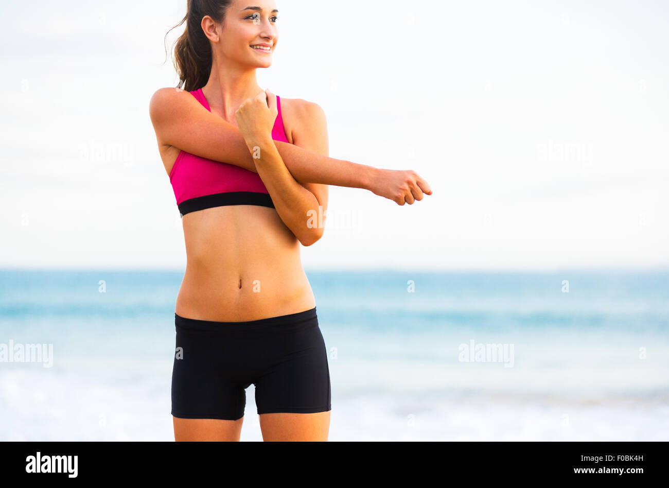 Young Attractive Fitness Woman Stretching on the Beach, Working Out. Healthy Active Outdoor Lifestyle. - Stock Image