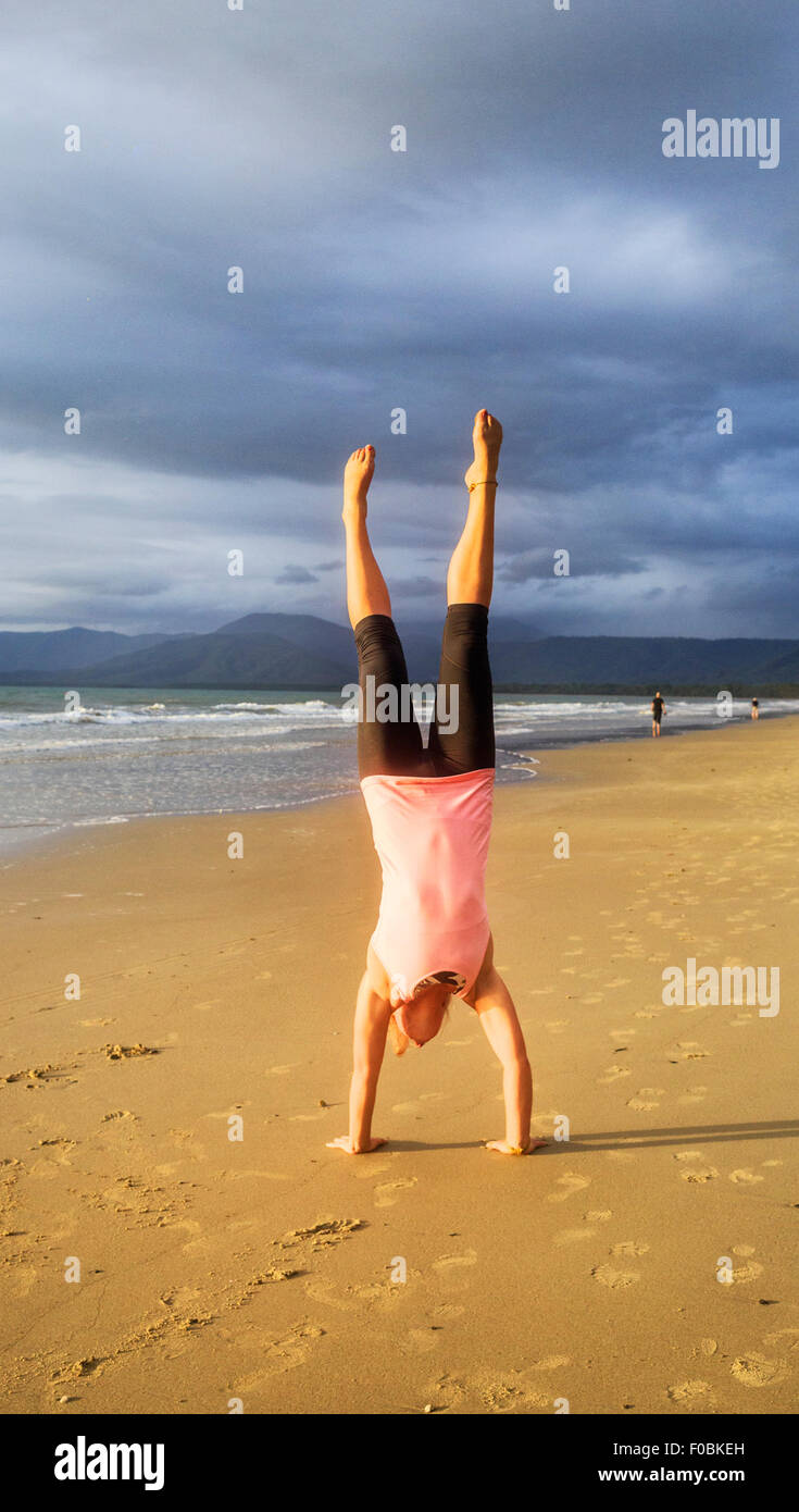 A young woman doing a handstand on beautiful tropical beach. Stock Photo