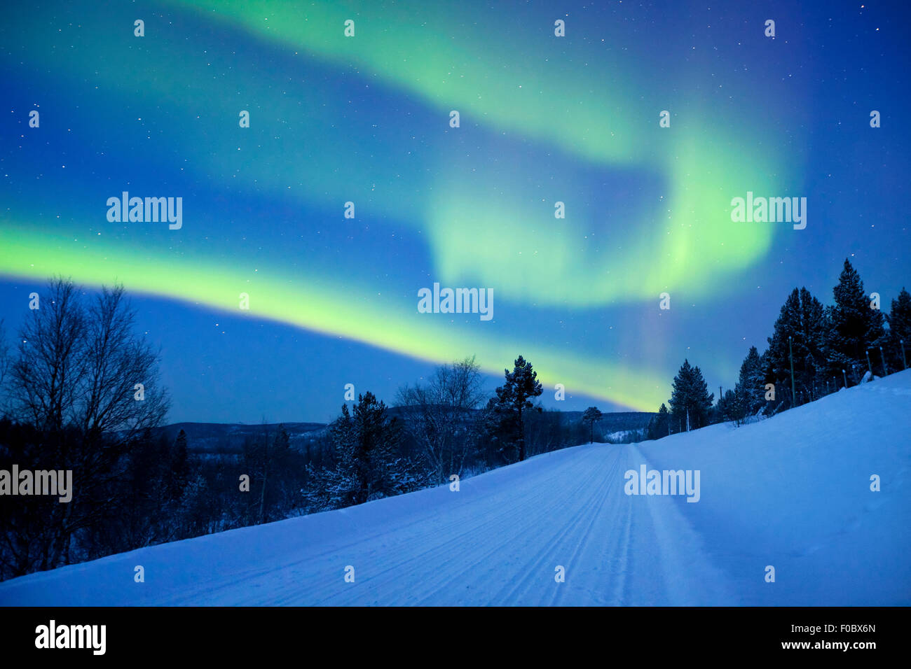 Spectacular aurora borealis (northern lights) over a road through winter landscape in Finnish Lapland. - Stock Image