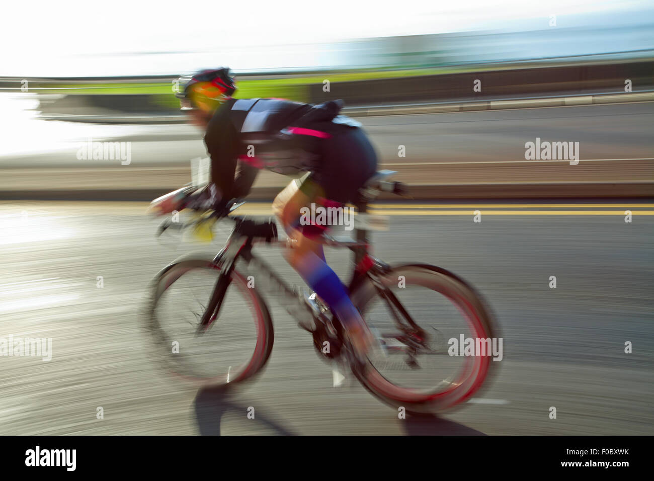 Athlet riding bicycle at sunny day on coastal road, blurred motion - Stock Image