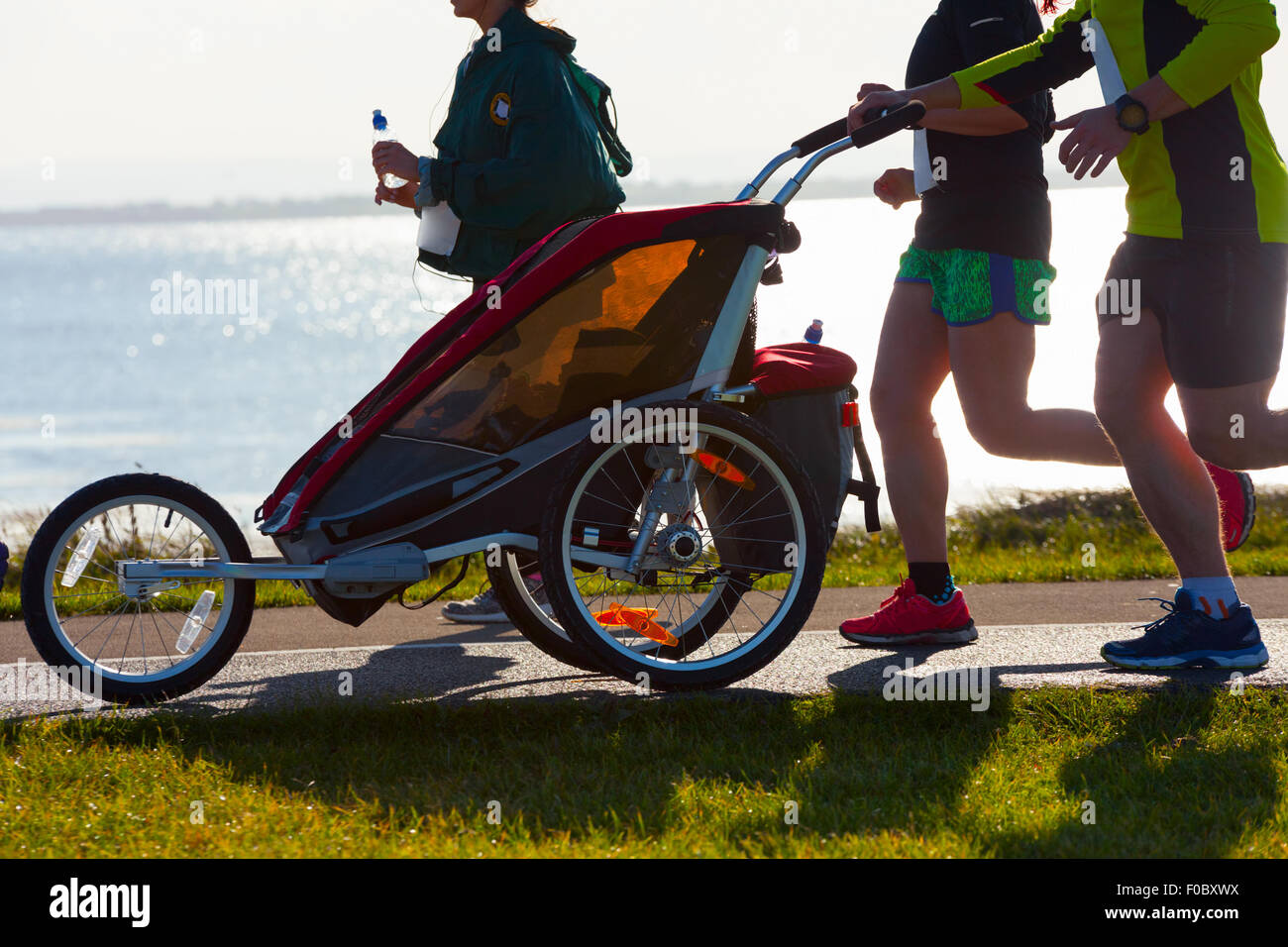 Group of runners with child, compete in the race on coastal road - Stock Image