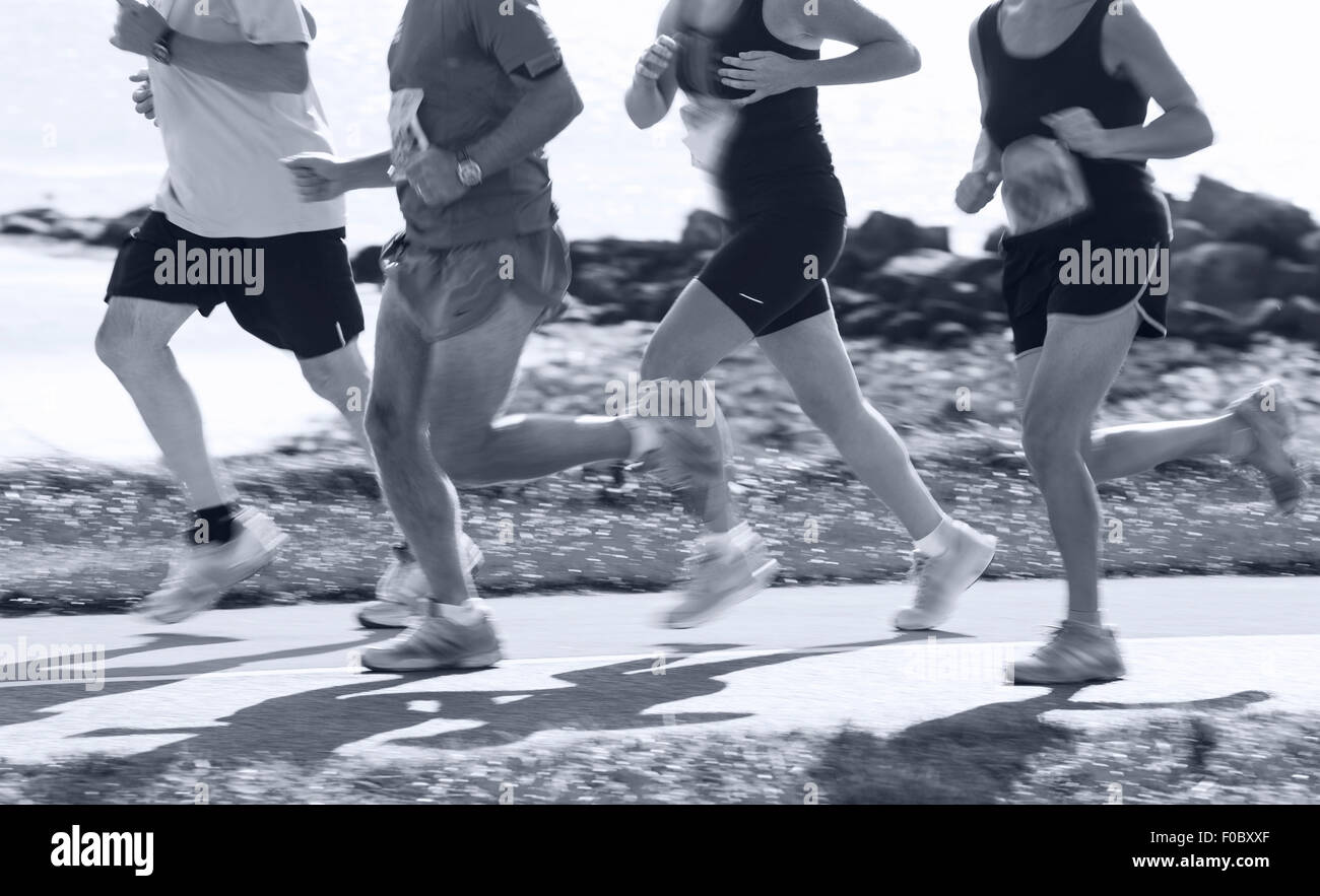 Group of runners compete in the race on coastal road. Blurred motion - Stock Image