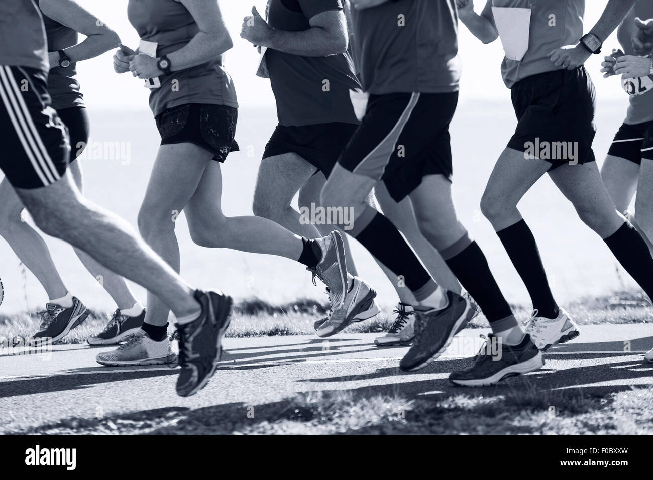 Group of runners compete in the race on coastal road - Stock Image