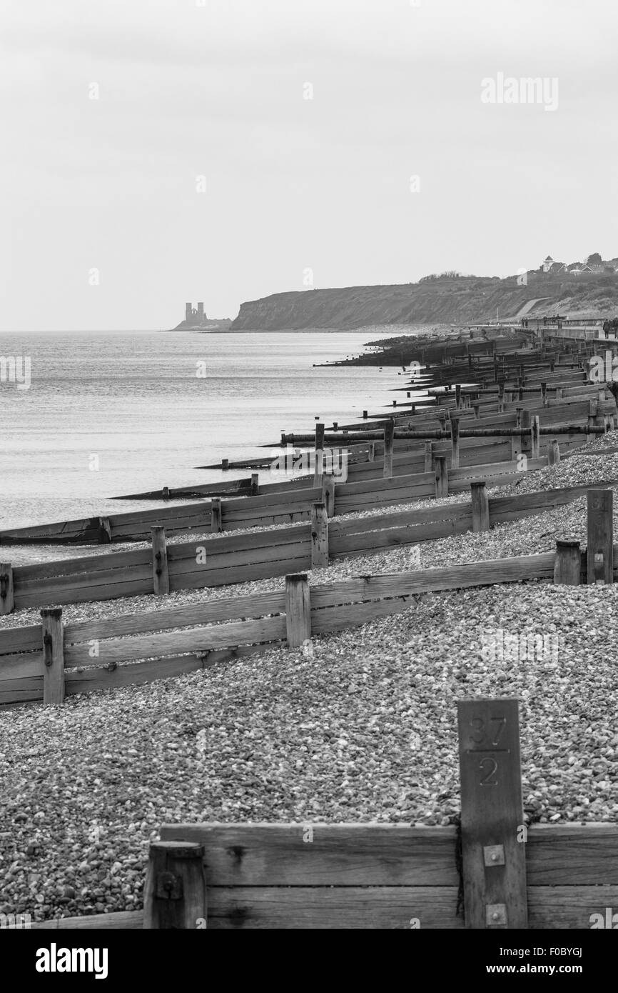 Groynes on Herne Bay Beach and Reculver Towers in the distance, Herne Bay, Kent, England, United Kingdom Stock Photo