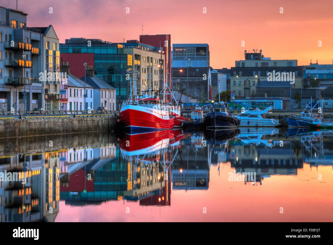 morning view on row of buildings and fishing boats in Galway Dock with sky reflected in the water, HDR image - Stock Image