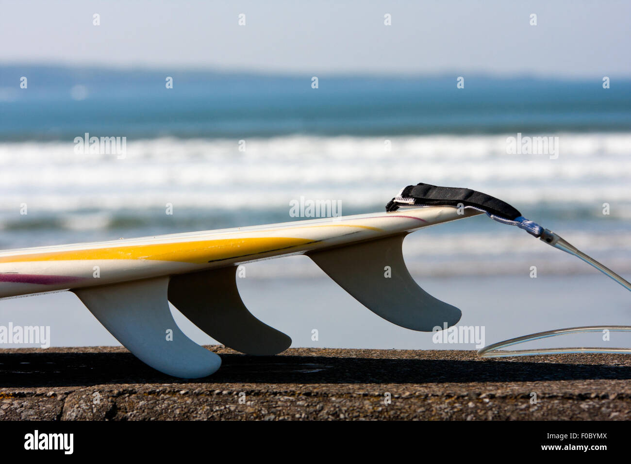 Surfboard with fins and waves on background, detail - Stock Image