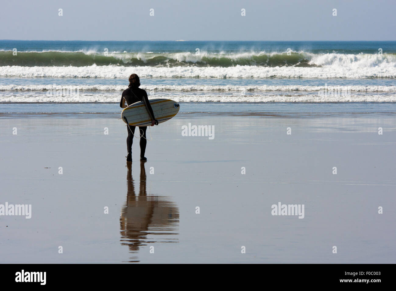 Man with surfboard watching Waves at Lahinch beach, Ireland - Stock Image