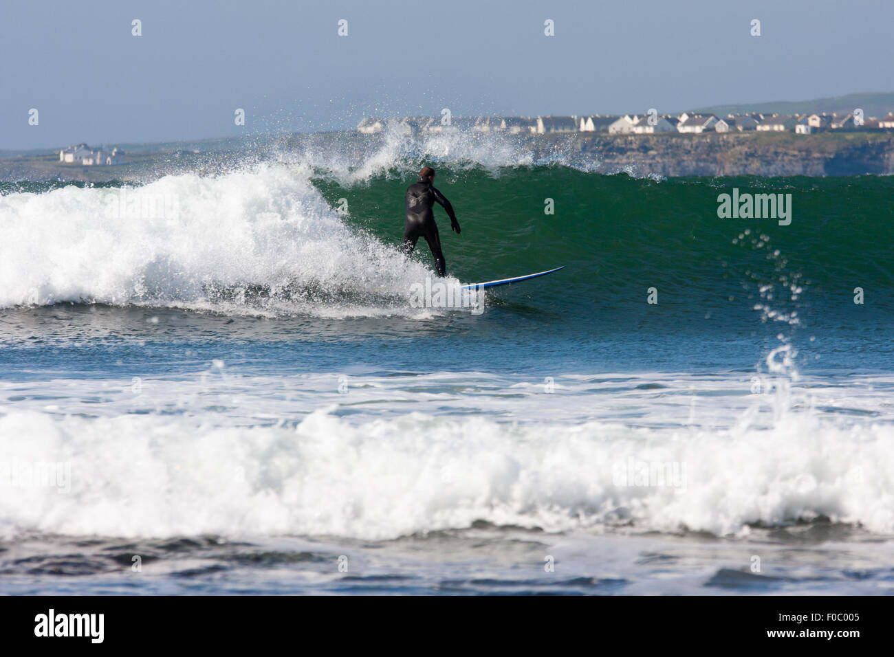 Surfing the Waves off Lahinch beach, Ireland - Stock Image