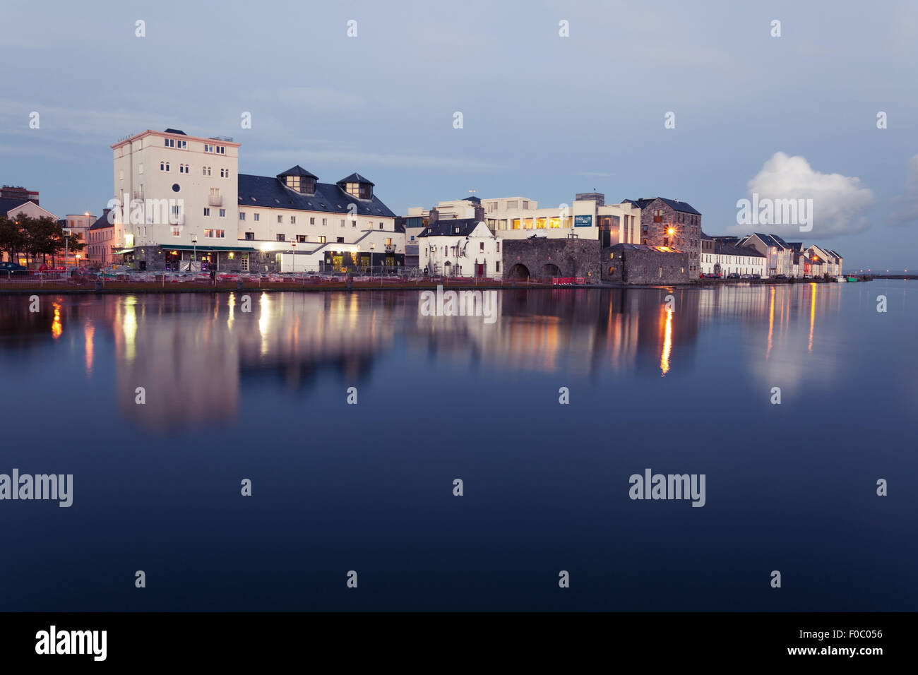 Buildings on the bank of the river during High tide in the city in dusk. Claddach, Galway, Ireland. - Stock Image
