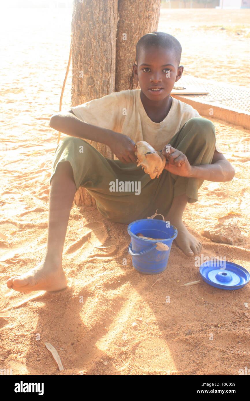 BANDIAGARA, MALI - SEPTEMBER 30, 2008:  Unidentified boy eating in bandiagara in the Mopti region in Mali on september Stock Photo