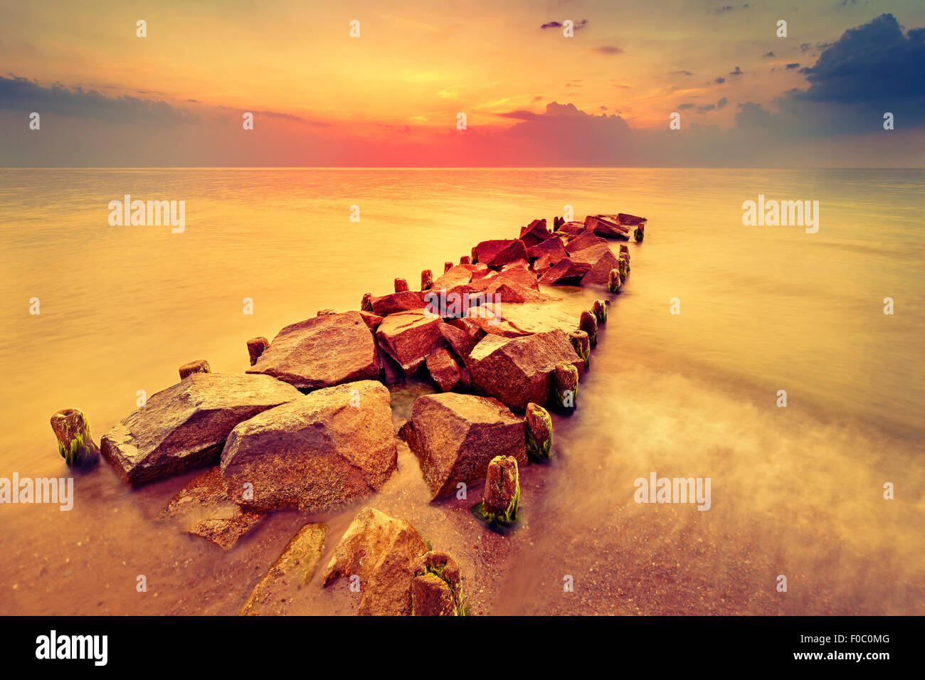 Beautiful sunset over beach and rocky pier. - Stock Image