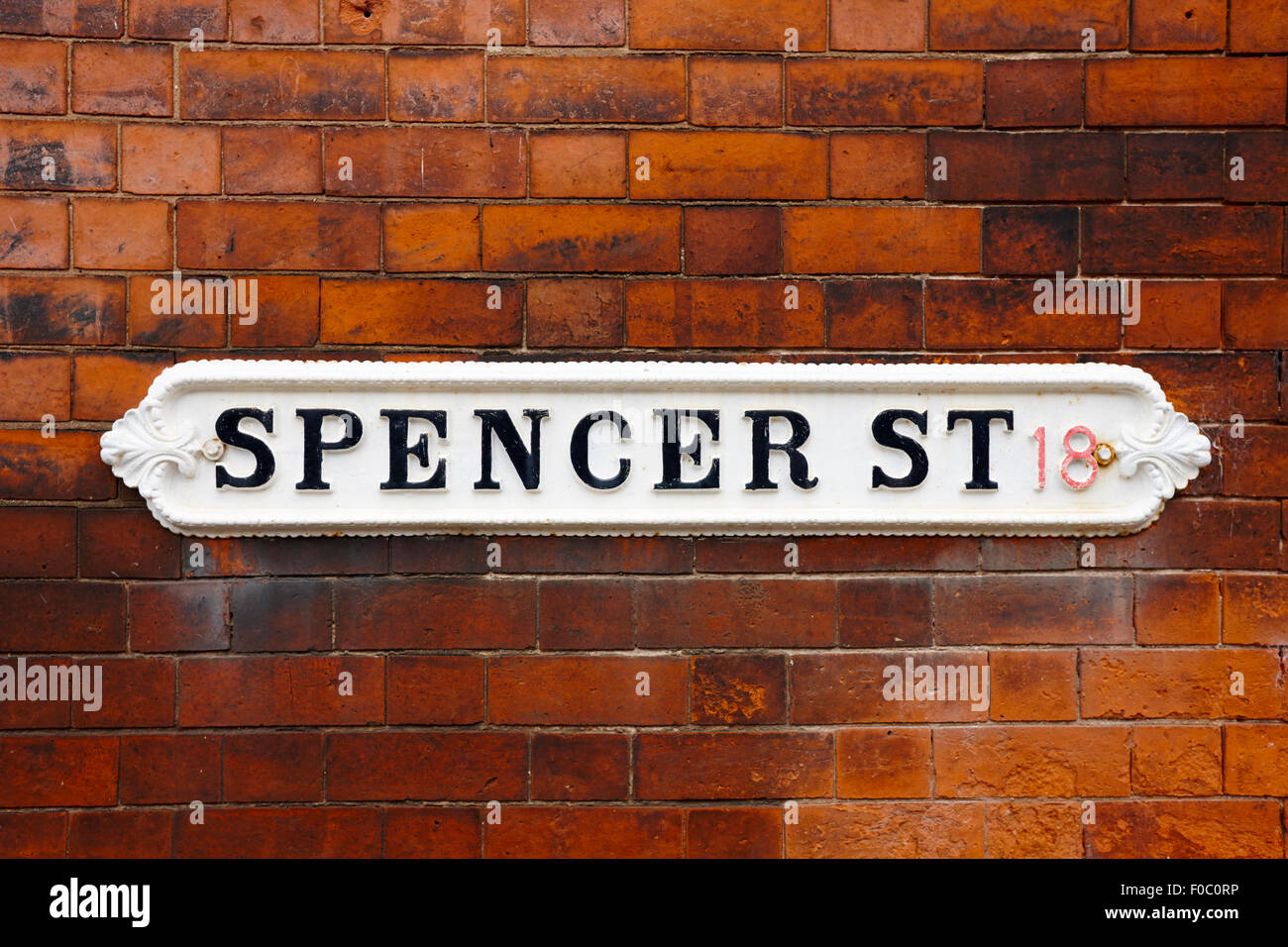 victorian metal street sign for spencer street on red brick building in the jewellery quarter Birmingham UK - Stock Image