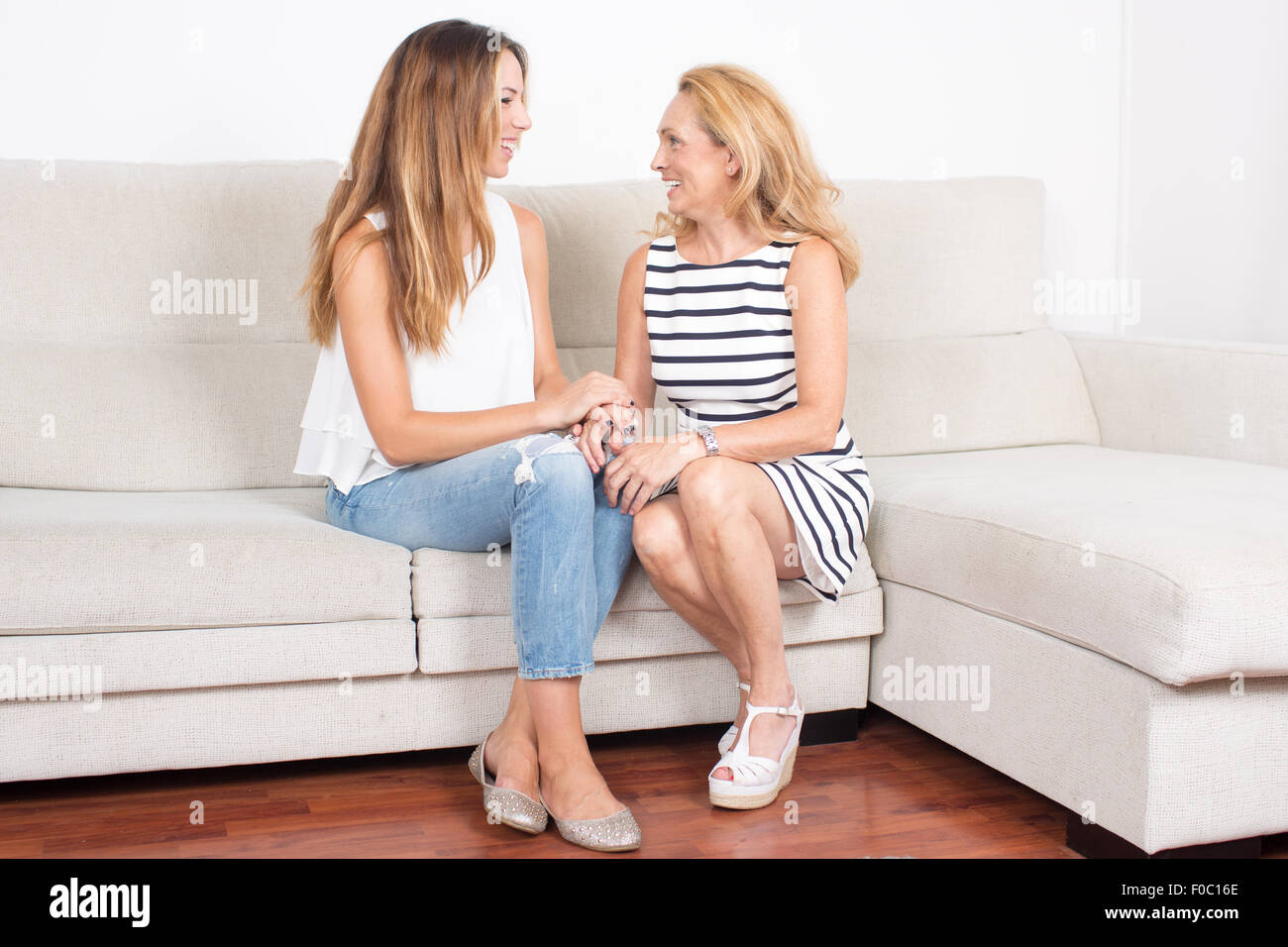 Elderly woman talking with a younger woman in the living room - Stock Image
