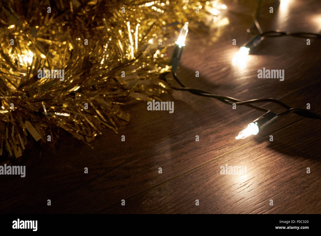 Traditional Christmas Tree lights and tinsel lying on a wooden floor. - Stock Image