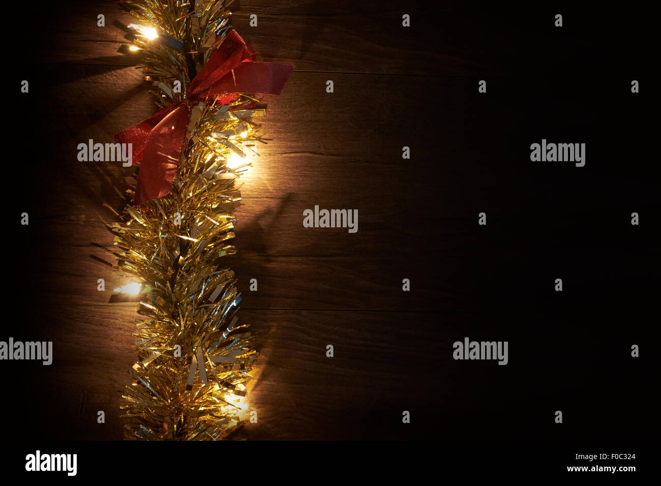 Traditional Christmas Tree lights, tinsel and ribbon lying on a wooden floor. - Stock Image