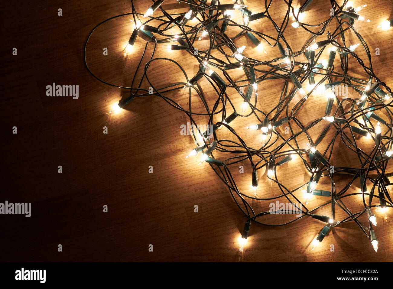 Traditional Christmas Tree lights lying on a wooden floor. - Stock Image