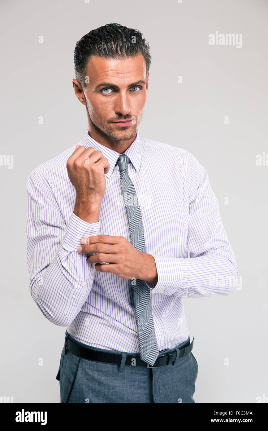 Handsome businessman buttoning cuff sleeves isolated on a white background - Stock Image