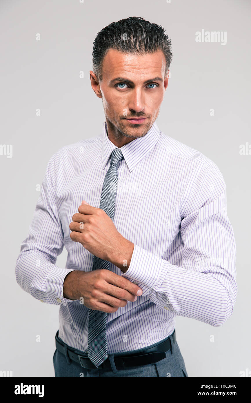 Confident businessman buttoning cuff sleeves isolated on a white background - Stock Image
