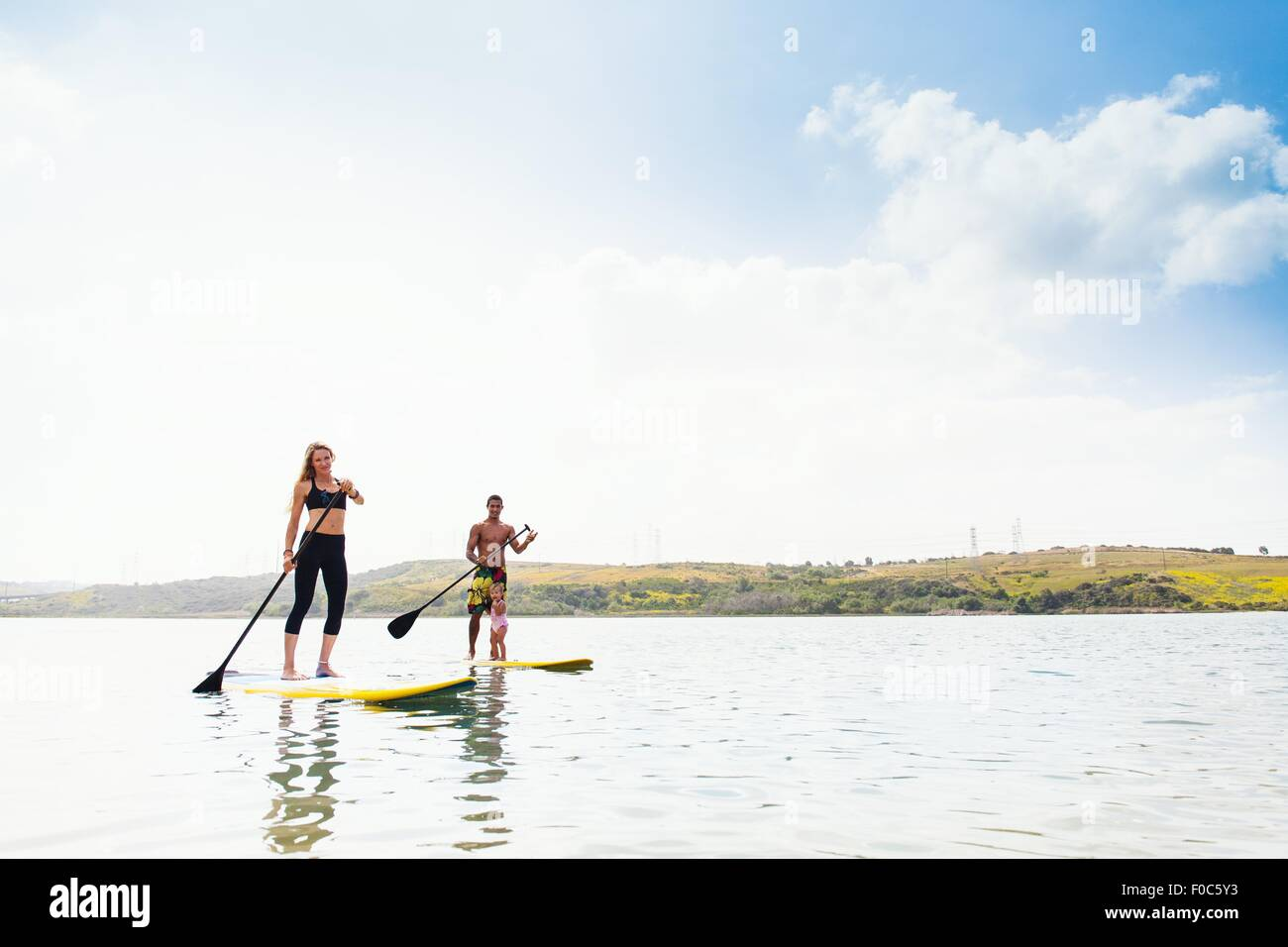Couple and toddler daughter standup paddleboarding on tranquil sea, Carlsbad, California, USA - Stock Image