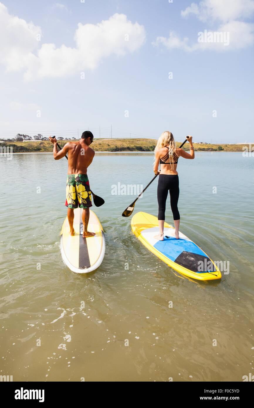 Rear view of couple standup paddleboarding, Carlsbad, California, USA - Stock Image