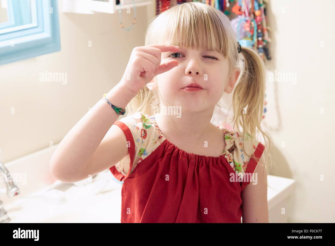 Portrait of young girl, looking through fingers - Stock Image