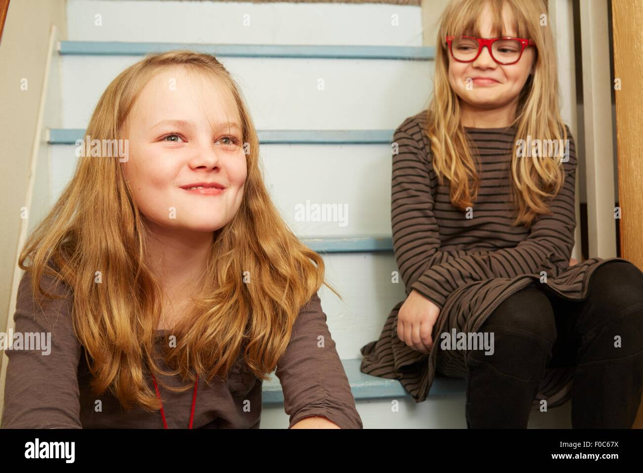 Two sisters sitting on stairs, smiling - Stock Image