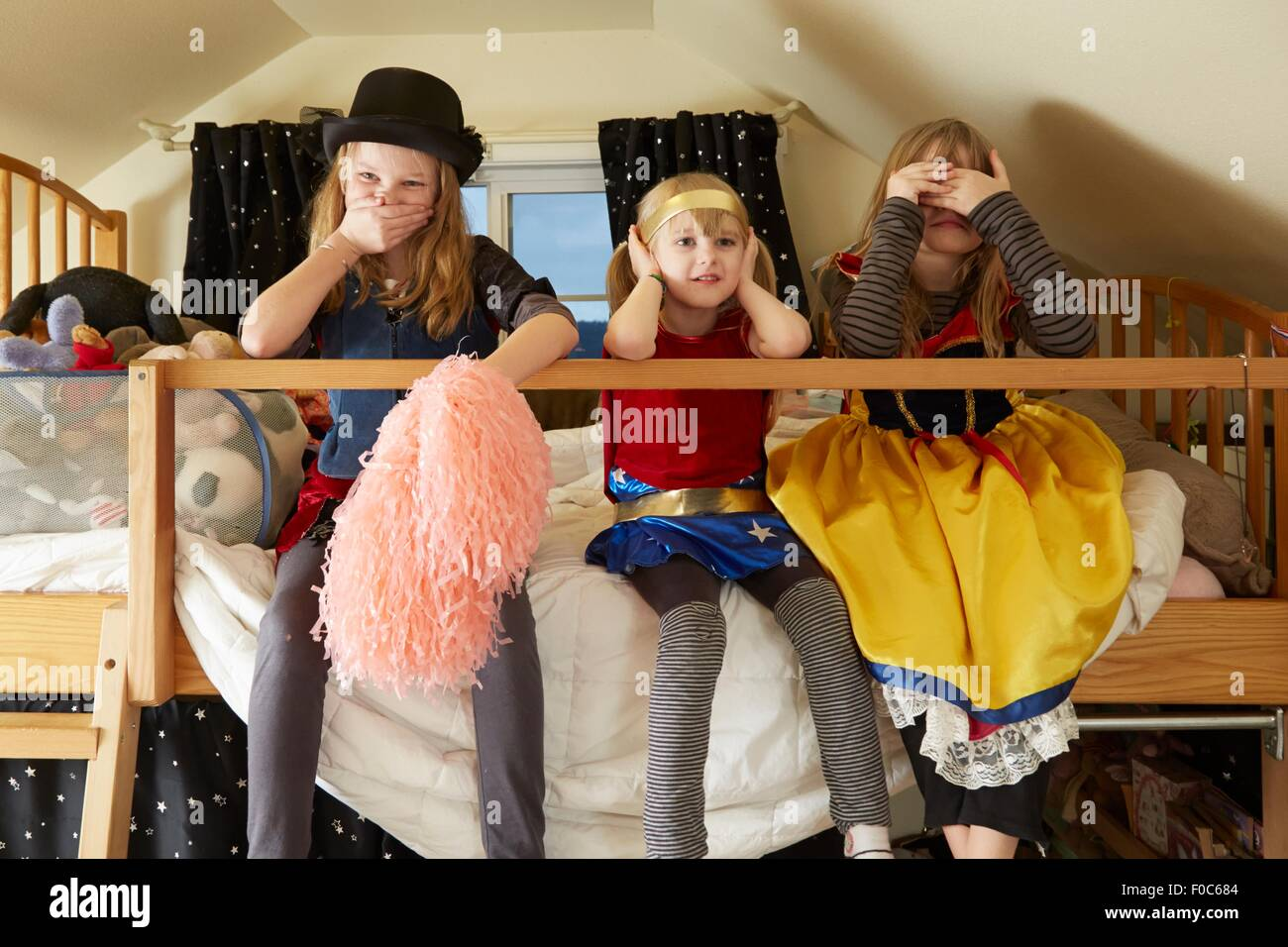 Three sisters, sitting on bed,  wearing fancy dress costumes, covering mouth, ears and eyes - Stock Image