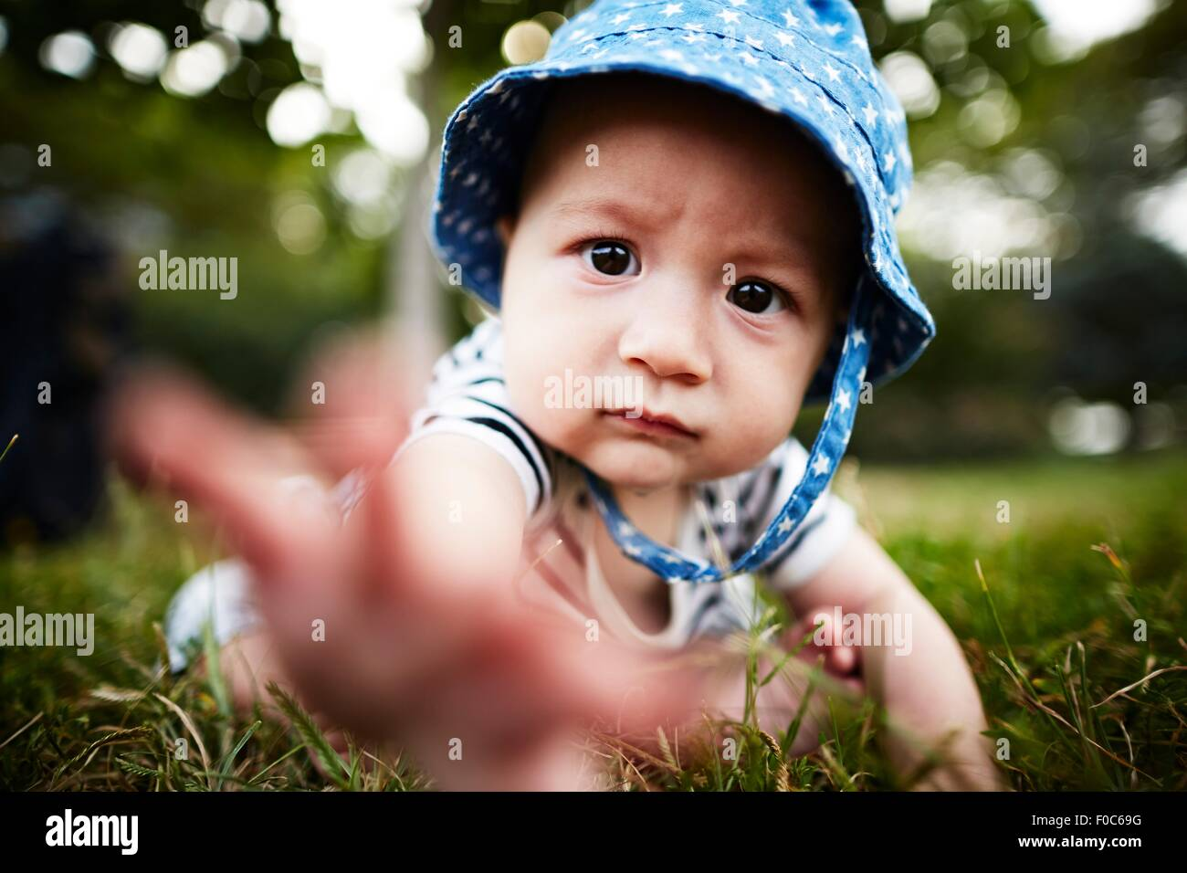 Close up of baby boy reaching out towards camera - Stock Image