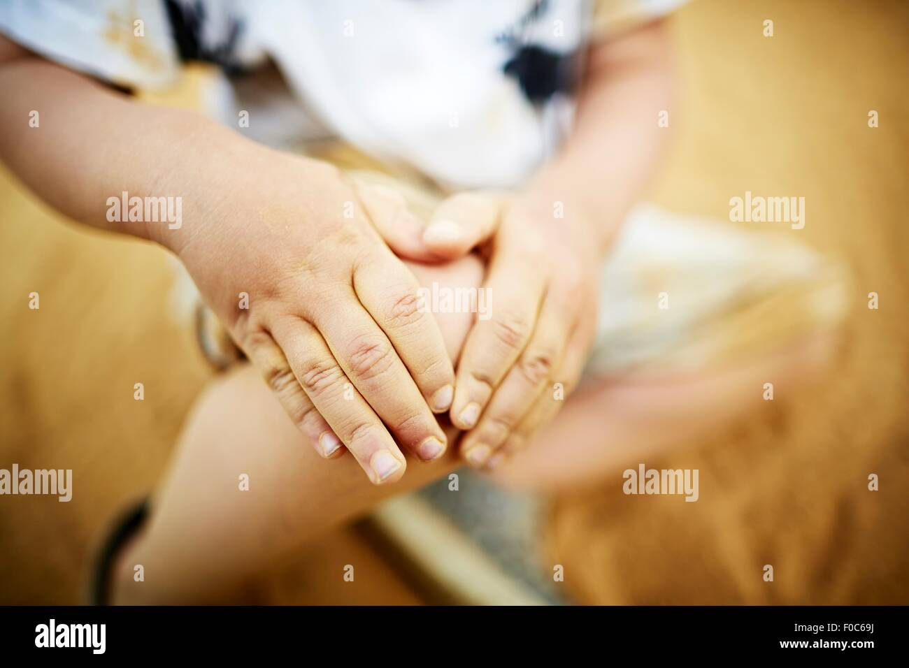 Close up of boy holding his knee with his hands - Stock Image