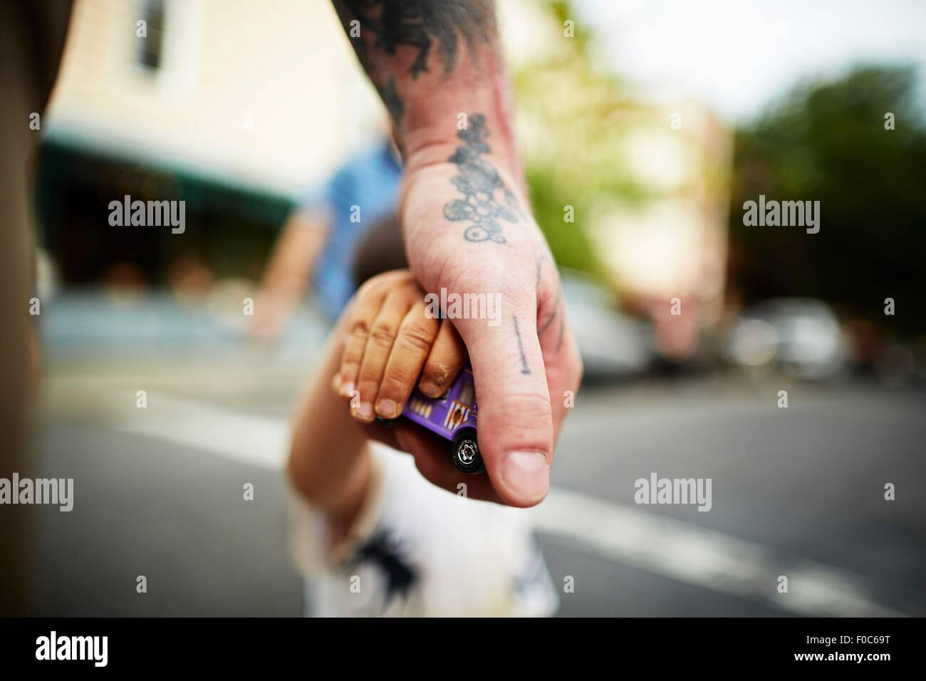 Close up of man holding boy's hand and toy crossing road - Stock Image