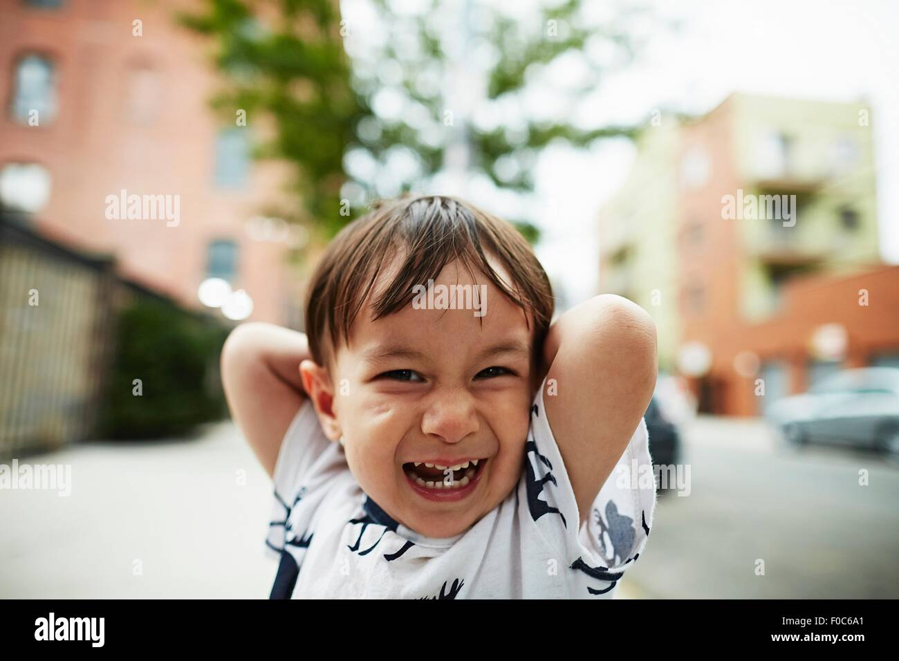 Portrait of laughing boy with his hands behind his head - Stock Image