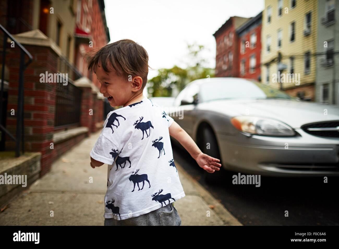 Boy running down street - Stock Image
