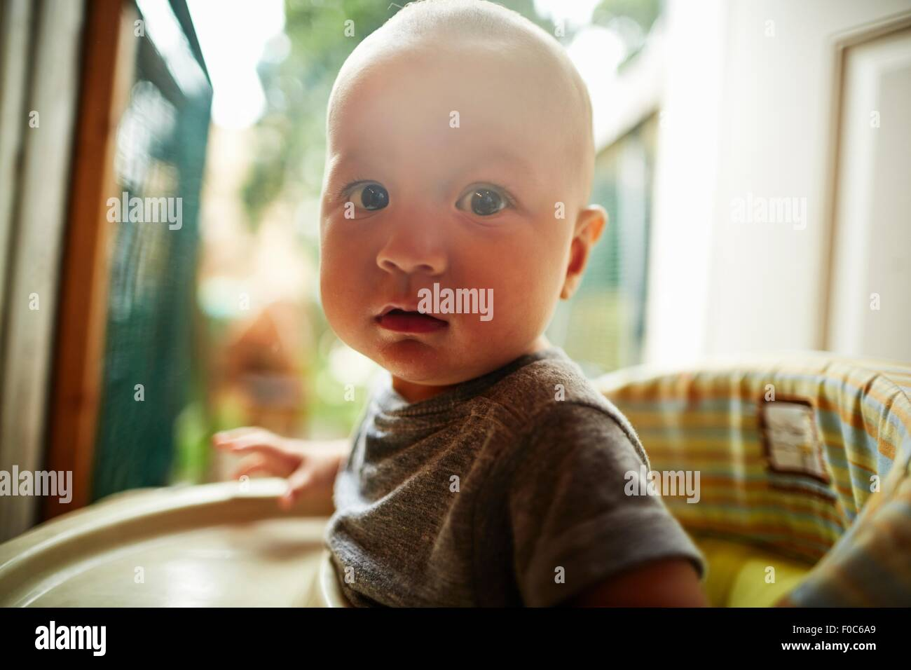 Portrait of baby boy looking at camera sitting in high chair - Stock Image