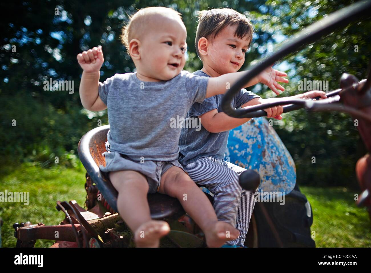 Baby boy and boy playing on old tractor Stock Photo