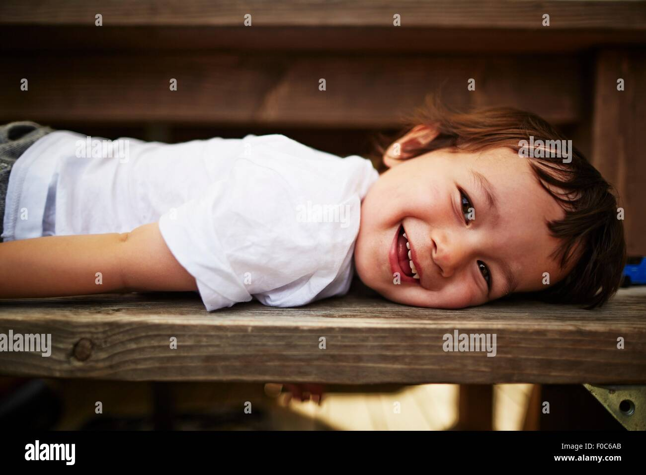 Portrait of smiling boy laying on bench - Stock Image