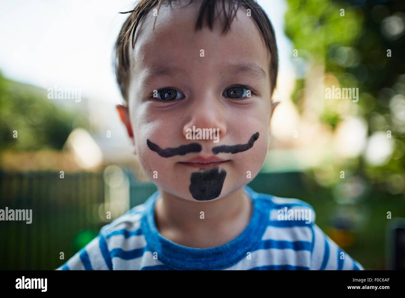 Close up portrait of boy looking at camera wearing beard and moustache face paint costume Stock Photo