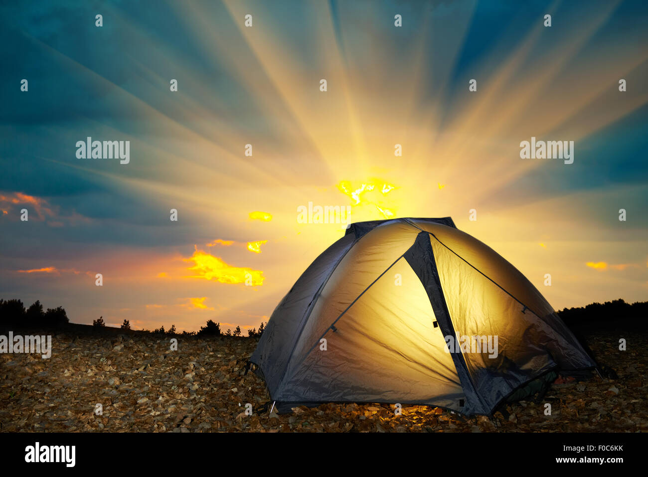 Illuminated yellow camping tent under stars at night. Instagram like filter - Stock Image