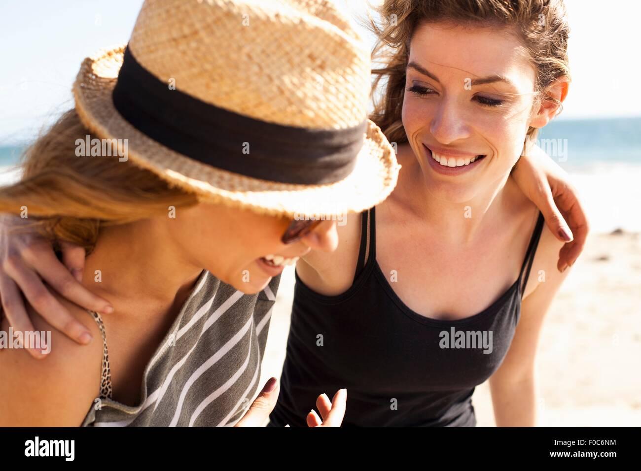 Girlfriends relaxing on beach - Stock Image