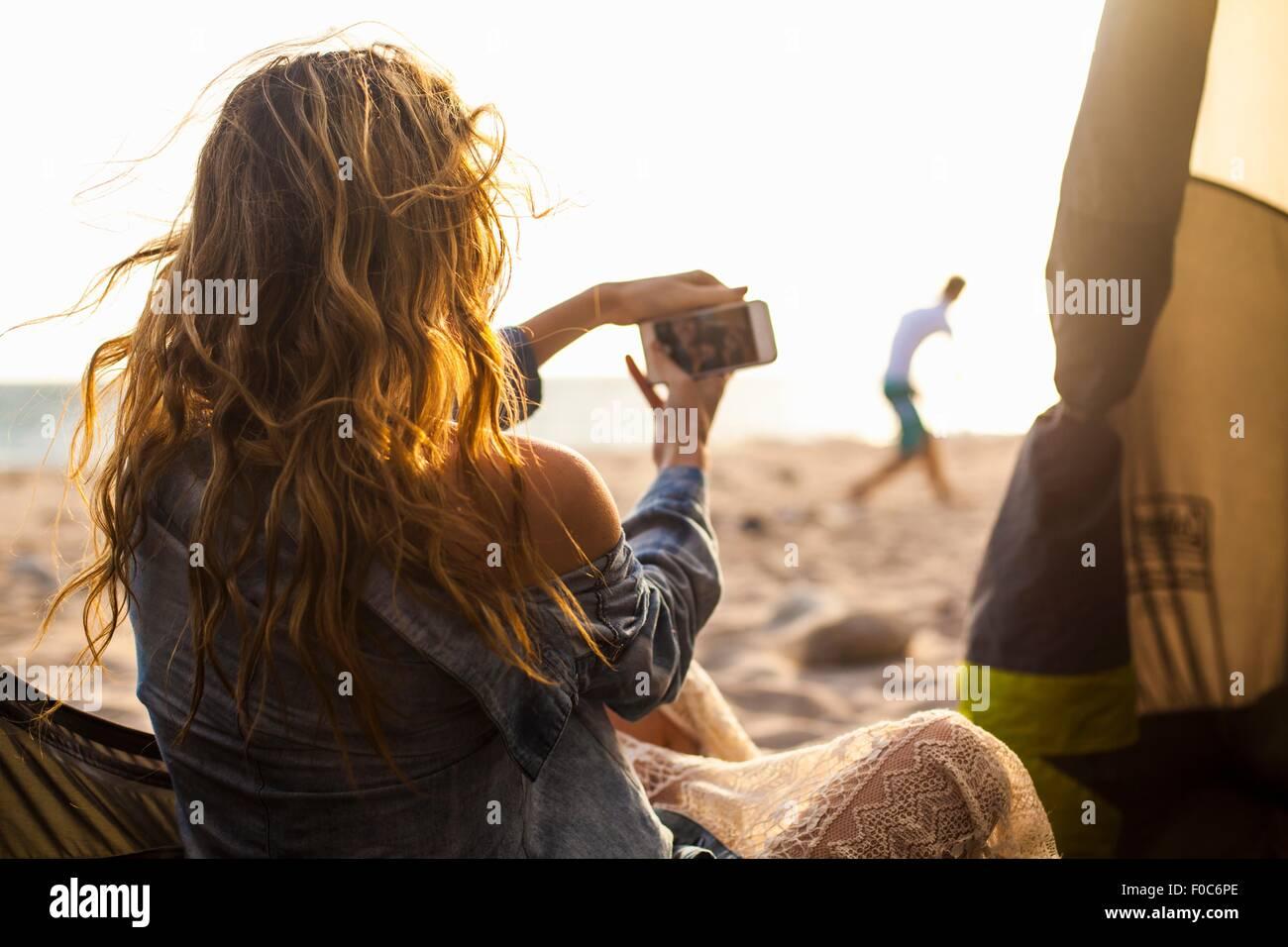 Woman taking photograph on beach - Stock Image