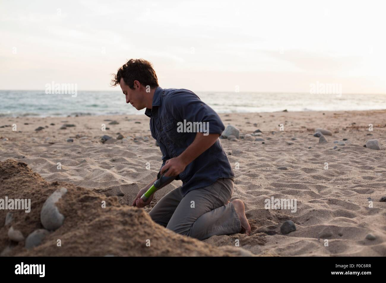 Man digging into sand on beach - Stock Image