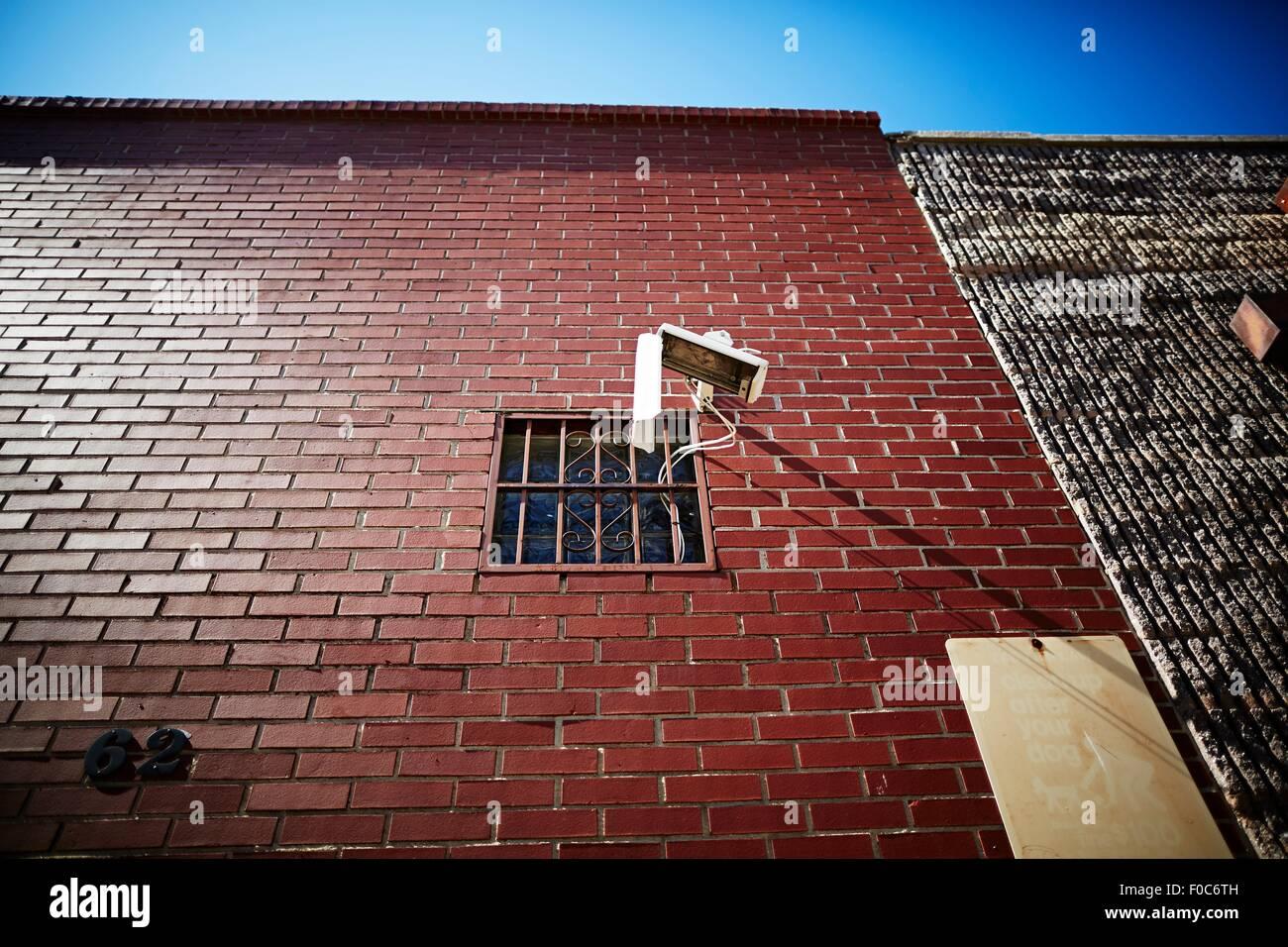 Surveillance camera on red brick wall - Stock Image