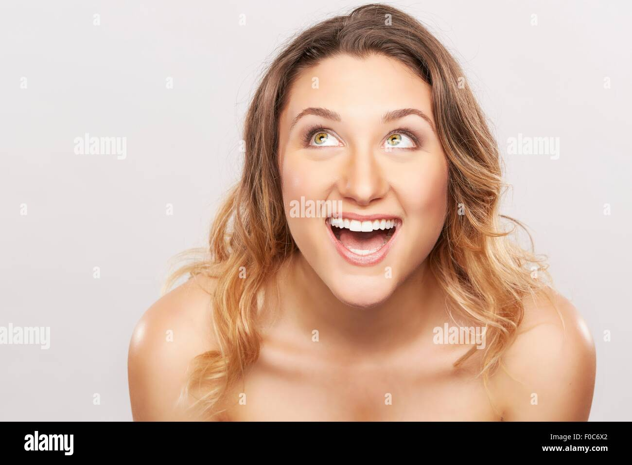 Young woman with bare shoulders laughing - Stock Image