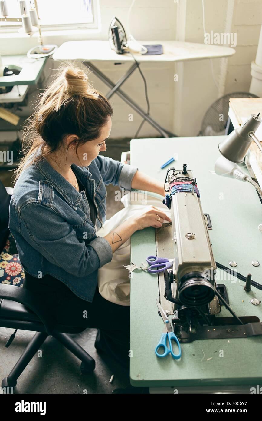 Female seamstress using sewing machine in fashion studio - Stock Image