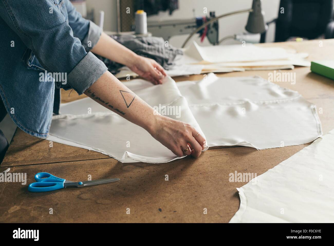 Young female seamstress folding pattern component in fashion studio - Stock Image