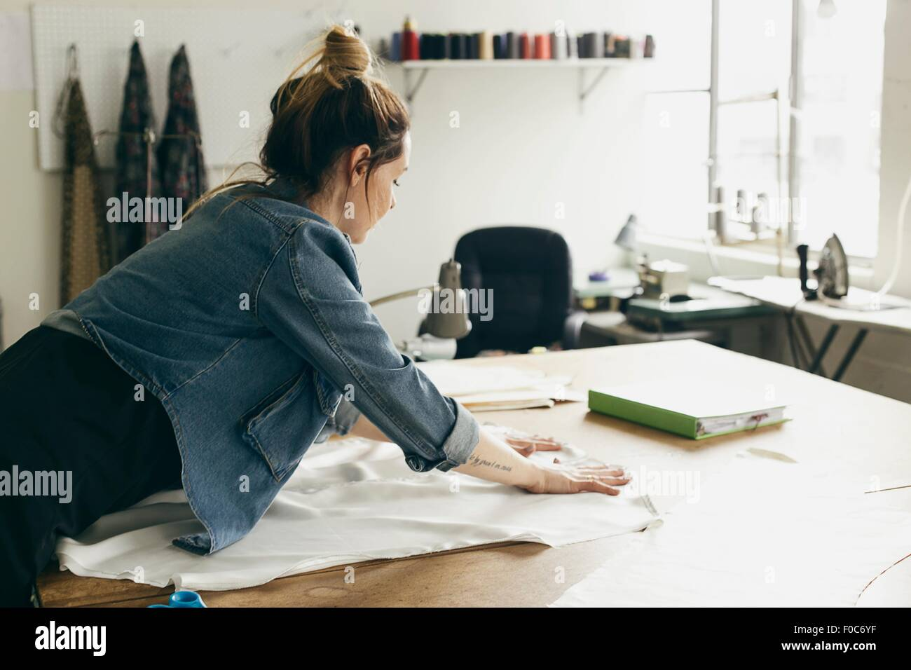 Young female seamstress laying out pattern component in fashion studio - Stock Image