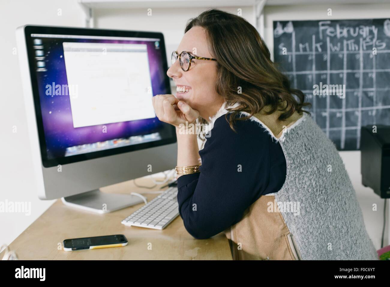 Portrait of young female office worker daydreaming at desk - Stock Image