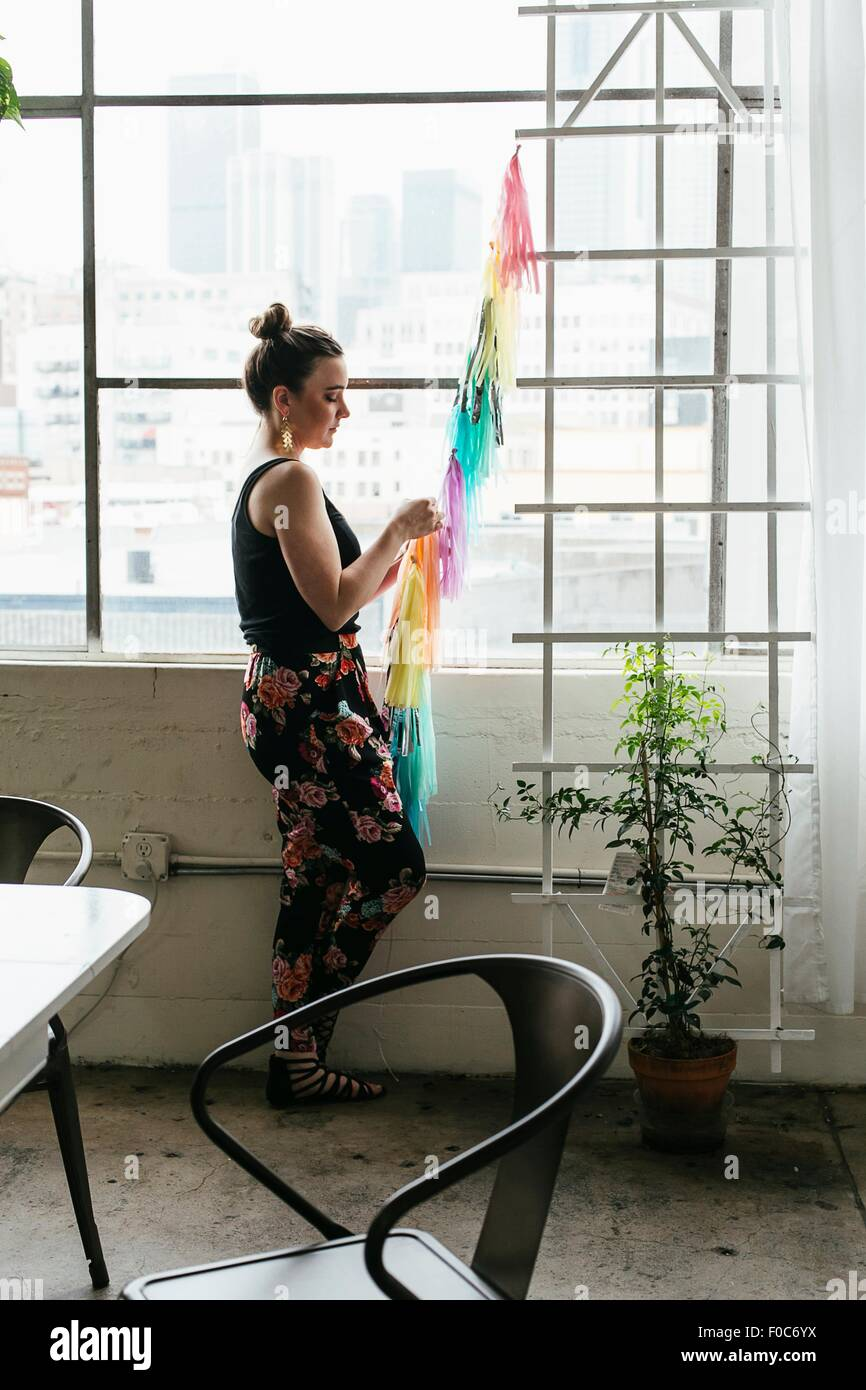 Young female designer making multi colored bunting in design studio - Stock Image