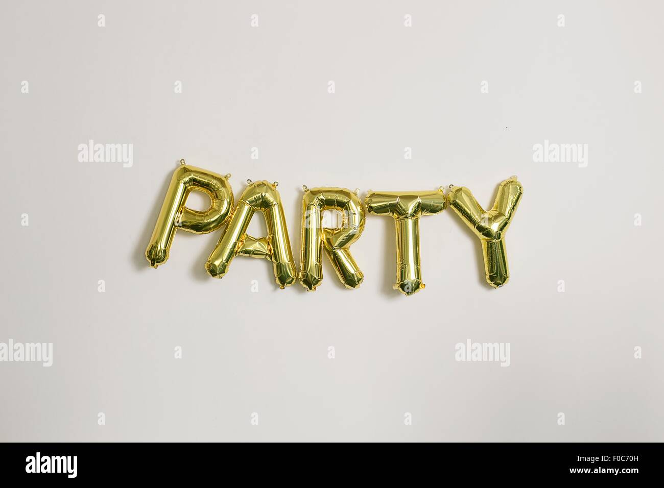Word party in gold inflatable capital letters - Stock Image